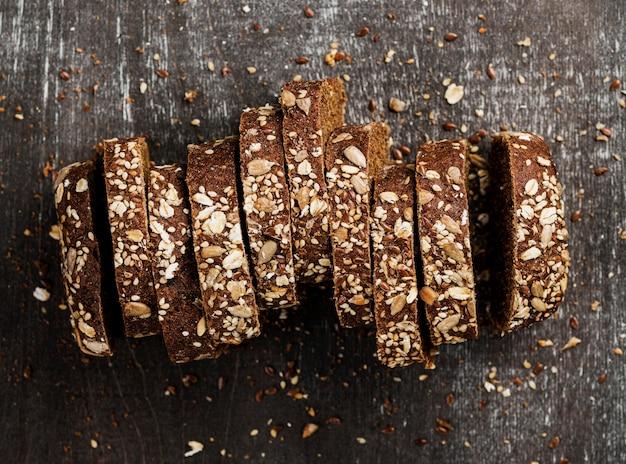 Vista superior close-up fatias de pão integral e fundo de madeira Foto gratuita