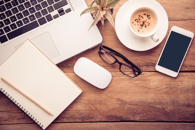 Vista superior com espaço de cópia, mesa de trabalho com laptop, celular, lápis de caderno e café Foto Premium
