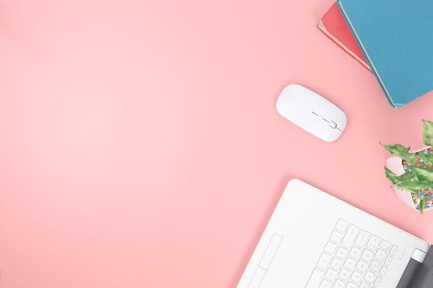 Vista superior com sobrecarga de livros de caderno de laptop em fundo rosa pastel, plana Foto Premium