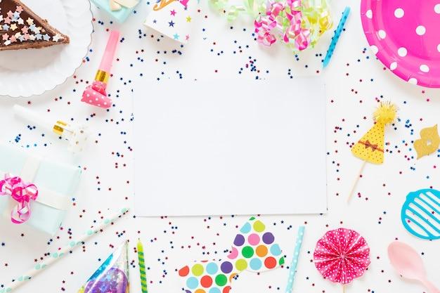 Vista superior composição de itens de aniversário festivo com cartão vazio Foto gratuita