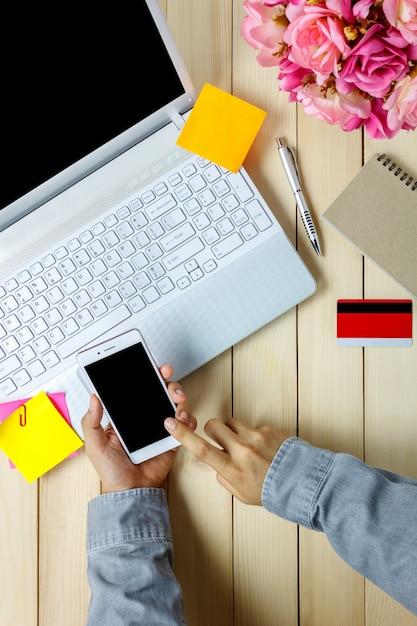 Vista superior conceito de escritório de negócios pessoa de negócios usando telefones celulares com laptop e cartão de crédito, caderno, flor na mesa de escritório. Foto Premium