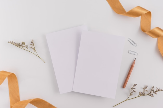 Vista superior, configuração lisa, cartão do convite do casamento, envelopes, papéis de cartões no fundo branco. Foto Premium