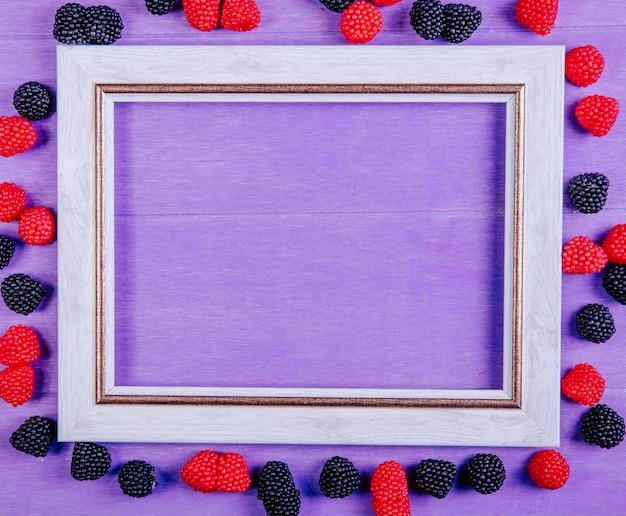 Vista superior cópia espaço cinza moldura com marmeladas em forma de framboesas e amoras em um fundo roxo Foto gratuita