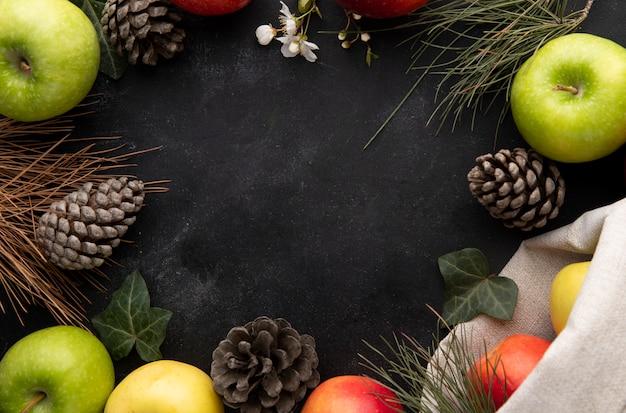 Vista superior cópia espaço maçãs coloridas e cones de abeto nas bordas em um fundo preto Foto gratuita