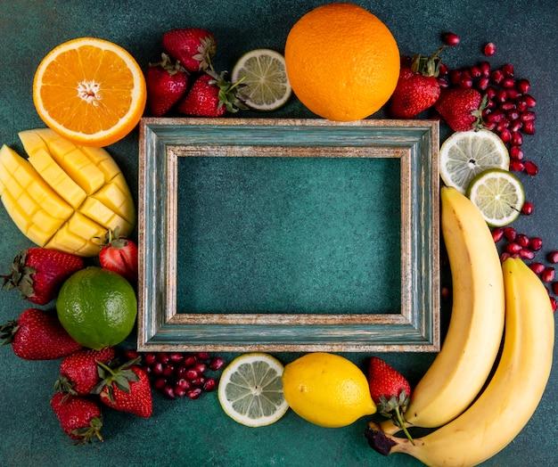 Vista superior cópia espaço mix de frutas manga banana morangos limão laranja com moldura em verde Foto gratuita