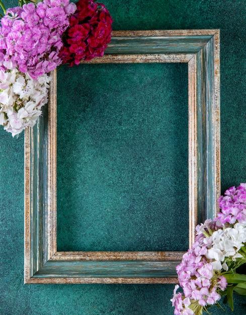 Vista superior cópia espaço quadro verde-dourado com flores coloridas nas bordas em verde Foto gratuita