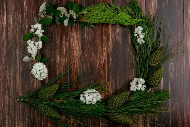 Vista superior cópia espaço spruce filial com cones com flores brancas nas bordas em um fundo de madeira Foto gratuita