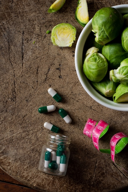 Vista superior couve de bruxelas com medicamento em cima da mesa Foto gratuita