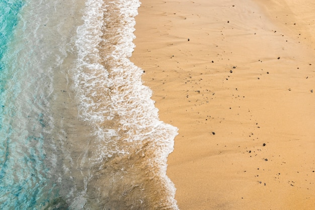 Vista superior da água do mar, tocando a areia na costa Foto gratuita