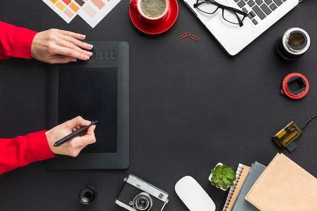 Vista superior da área de desenho com as mãos na mesa Foto gratuita