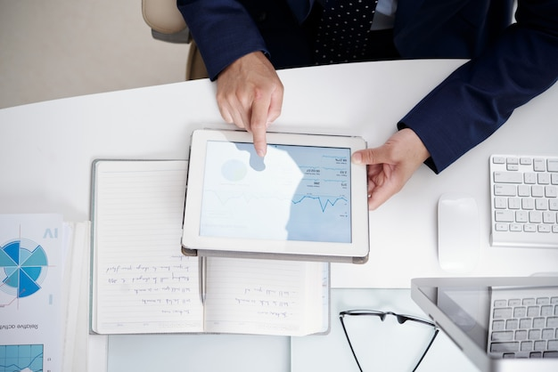 Vista superior da área de trabalho do escritório com notebook, documentos, computador e tablet digital usado por homem anônimo Foto gratuita