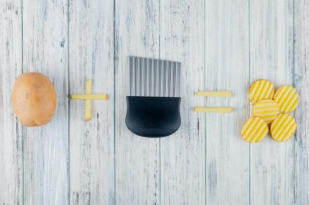 Vista superior da batata inteira e fatiada com cortador de batata no fundo de madeira com espaço de cópia Foto gratuita