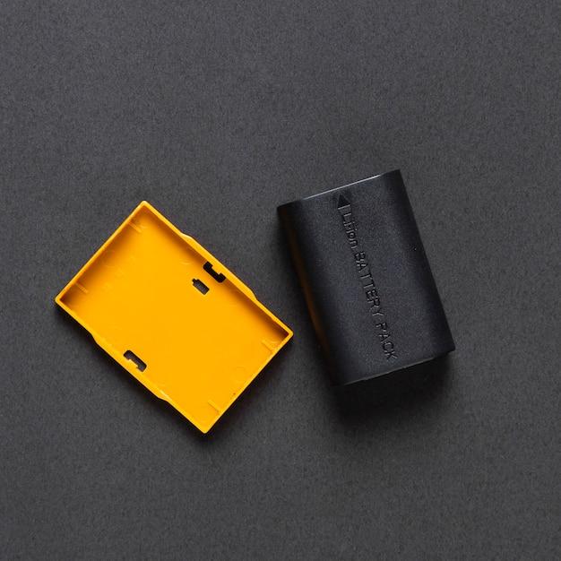 Vista superior da bateria da câmera em fundo preto Foto gratuita