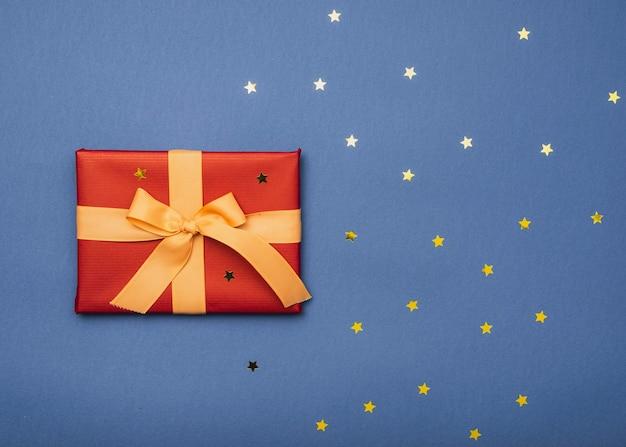 Vista superior da caixa de natal com estrelas douradas e fita Foto gratuita