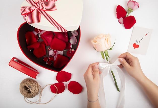 Vista superior da caixa de presente em forma de coração cheia de corda de grampeador de pétalas de rosa vermelha e mãos femininas, amarrando uma rosa branca com uma fita no fundo branco Foto gratuita