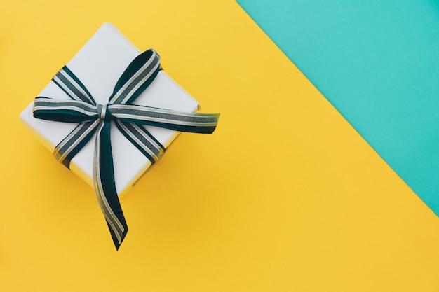 Vista superior da caixa de presente embrulhado branco decorado com laços de fita em fundo de papel amarelo e verde Foto Premium