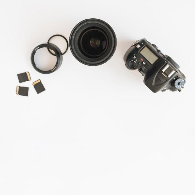 Vista superior da câmera dslr; cartões de memória e lente da câmera com anéis de extensão em pano de fundo branco Foto gratuita
