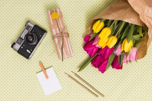 Vista superior da câmera retro; papel em branco; lápis; caixa de presente e buquê de flores de tulipa acima de fundo amarelo polka dot Foto gratuita