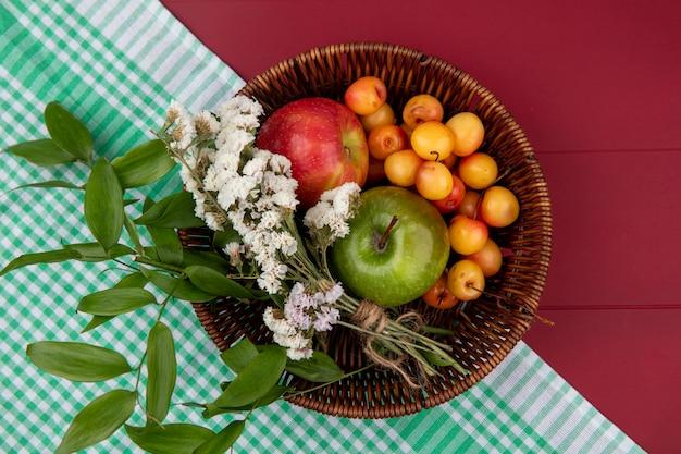 Vista superior da cereja branca com maçãs coloridas e flores em uma cesta sobre uma mesa vermelha Foto gratuita