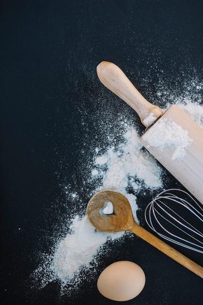 Vista superior da colher de forma de coração; bata; farinha; ovo e rolo em fundo preto Foto gratuita