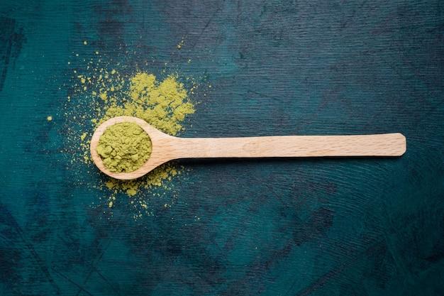 Vista superior da colher de pau de chá verde matcha em pó no fundo esmeralda. Foto Premium