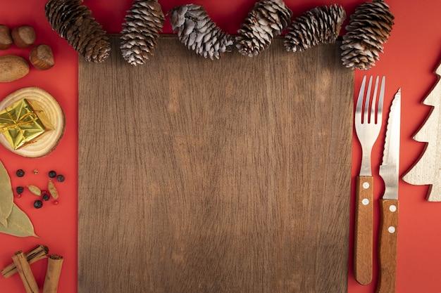Vista superior da configuração da mesa de natal com talheres e pinhas Foto gratuita