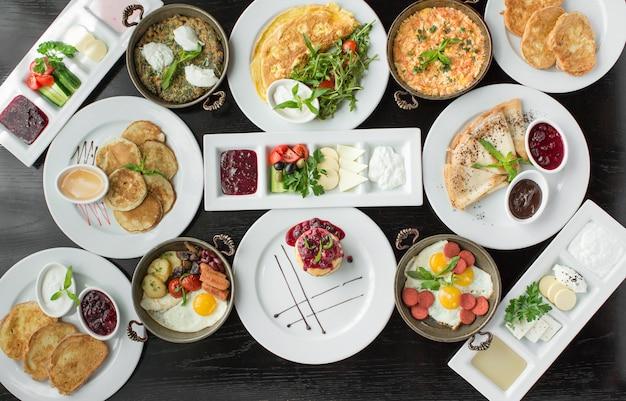 Vista superior da configuração de café da manhã com omelete, crepes, compotas, torradas, prato de salsicha Foto gratuita