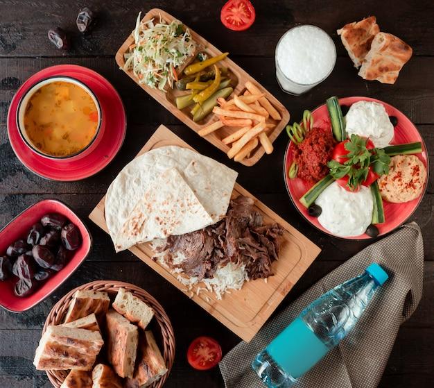 Vista superior da configuração do almoço com sopa, kebab e arroz e acompanhamentos Foto gratuita