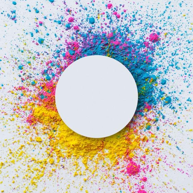 Vista superior da cor holi sobre um fundo branco com um círculo em branco Foto gratuita