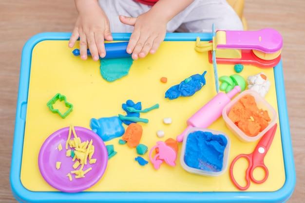 Vista superior da criança asiática de 2 anos de idade criança bebê menino se divertindo jogando argila de modelagem colorida / brincou dought, cozinhar brinquedos na escola de brincar, brinquedos educativos jogo criativo para o conceito de crianças Foto Premium
