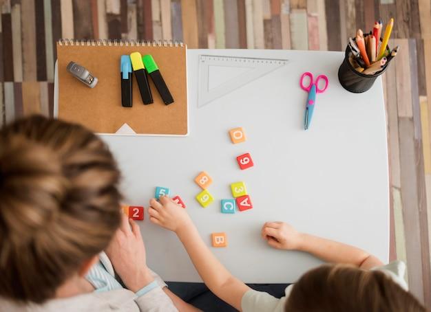 Vista superior da criança e do tutor aprendendo sobre números e letras Foto gratuita