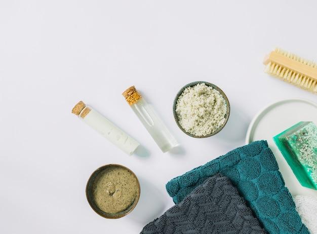 Vista superior da esfoliação herbal cosmética; escova; guardanapo e sabonete na superfície branca Foto gratuita