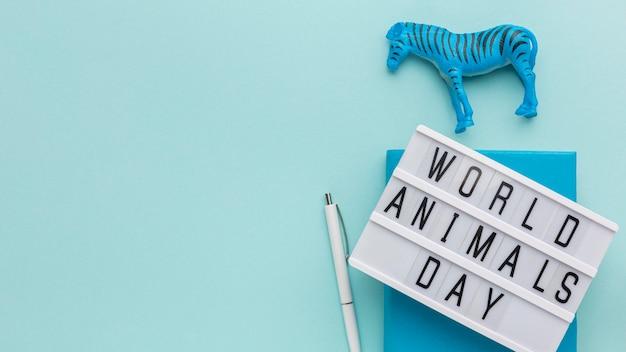Vista superior da estatueta de zebra com caixa de luz e caneta para o dia dos animais Foto gratuita