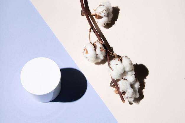 Vista superior da flor de algodão e creme Foto gratuita