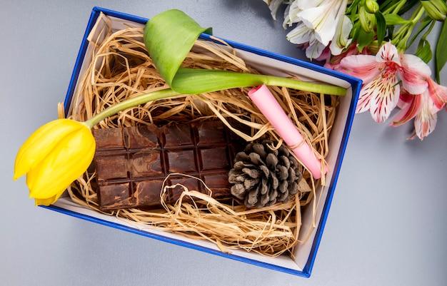 Vista superior da flor de tulipa de cor amarela com barra de chocolate escura e cone em um canudo em uma caixa de presente azul e um buquê de cores de alstroemeria na mesa branca Foto gratuita