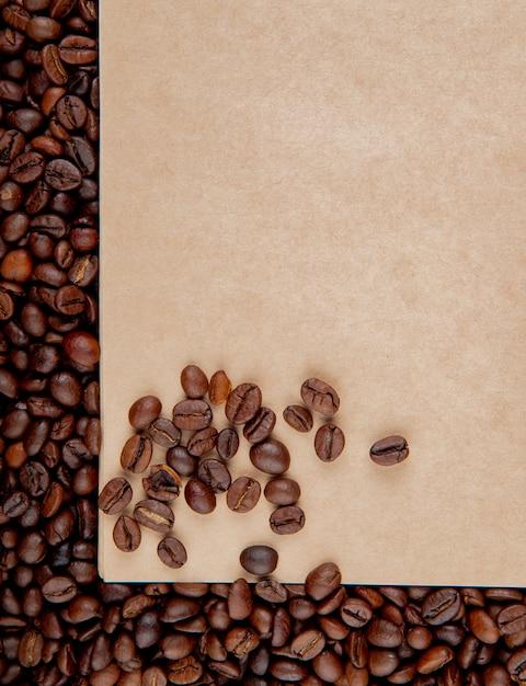 Vista superior da folha de papel ofício marrom no fundo de grãos de café Foto gratuita