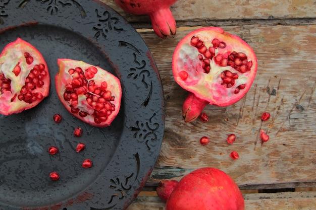 Vista superior da fruta romã madura na placa antiga Foto gratuita