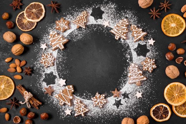 Vista superior da grinalda de biscoitos de gengibre com frutas cítricas e nozes secas Foto gratuita
