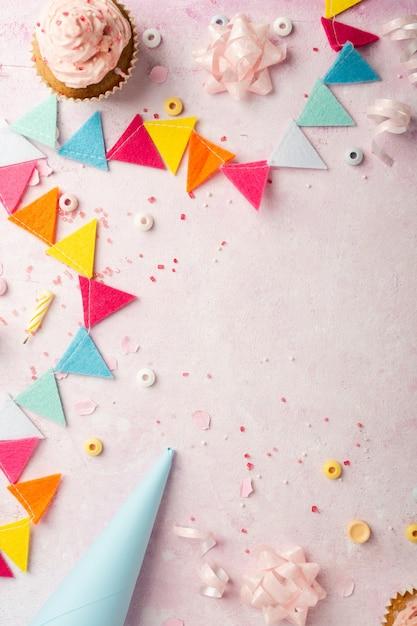 Vista superior da guirlanda de aniversário e cupcakes Foto gratuita