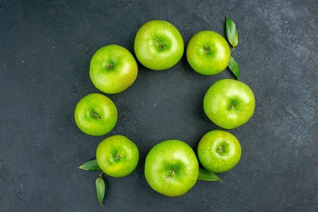 Vista superior da linha do círculo com maçãs verdes na mesa escura Foto gratuita