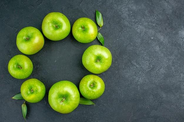 Vista superior da linha do círculo com maçãs verdes no espaço da cópia da mesa escura Foto gratuita