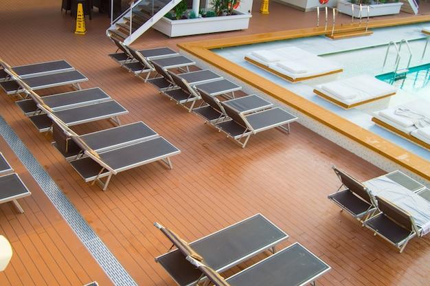 Vista superior da luxuosa piscina com espreguiçadeiras vazias no convés aberto de um cruzeiro moderno Foto Premium