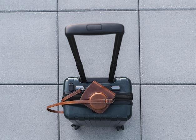 Vista superior da mala e câmera retro em estojo de couro Foto gratuita