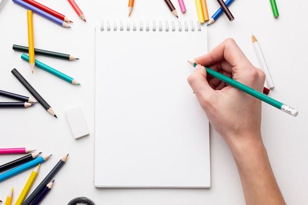 Vista superior da mão com lápis no notebook Foto gratuita