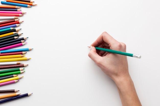 Vista superior da mão com lápis sobre papel Foto gratuita