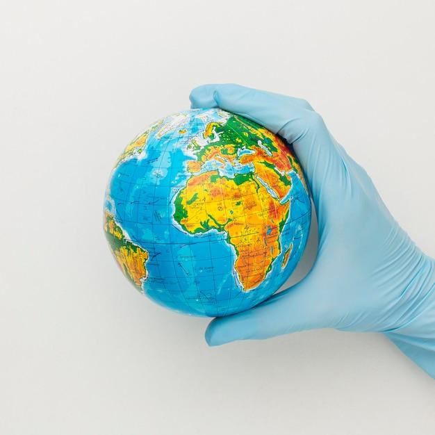 Vista superior da mão com luvas segurando o globo Foto gratuita