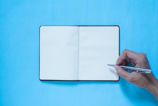 Vista superior da mão, escrevendo no caderno em azul e rosa pastel cor bakcground Foto Premium