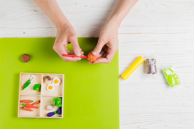 Vista superior da mão fazendo abóbora de barro laranja Foto gratuita