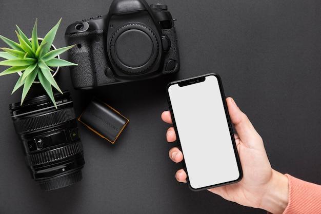 Vista superior da mão segurando um smartphone com câmera em fundo preto Foto gratuita