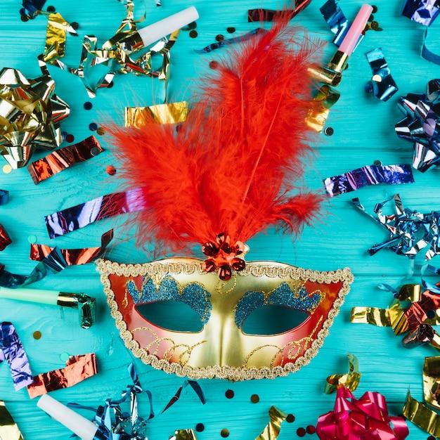 Vista superior da máscara de carnaval veneziano com penas em ouro e vermelho com material de decoração de festa Foto gratuita